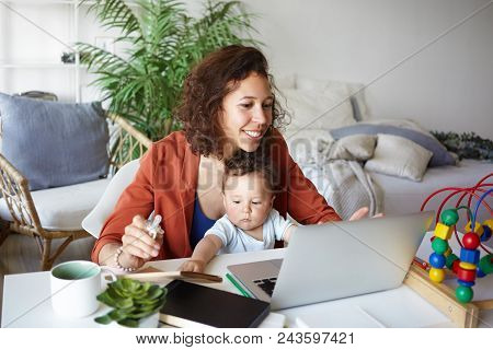 Attractive Young Dark Skinned Woman Working At Desk At Home Using Laptop, Holding Baby On Her Lap. P