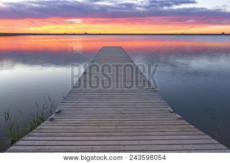 Sunrise Or Sunset Over A Fishing Dock Or Fishing Pier With Colorful Clouds Reflecting In The Lake Lo
