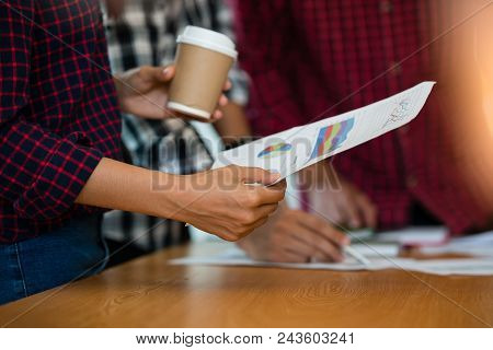 Hand Of Business Man Hold Graph Paper Charts, Market Reports During A Meeting In The Office. Busines