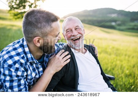 An Adult Hipster Son With His Senior Father In Wheelchair On A Walk On A Meadow In Nature At Sunset,