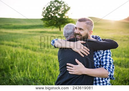 An Adult Hipster Son With His Senior Father On A Walk In Nature At Sunset, Hugging. Copy Space.