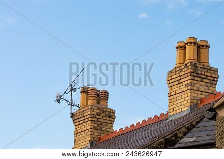 Old Residential Rooftop And Chimneys With Tv Ariel. Slate Roof, Decorative Red Terracotta Ridge Tile