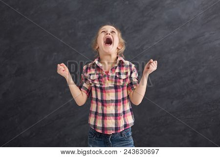 Angry Little Girl Crying At Dark Studio Background. Desperate Child Yelling, Emotional Stress Concep