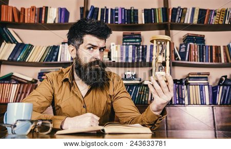 Library And Librarian. Man On Thoughtful Face Holds Hourglass While Studying, Bookshelves On Backgro