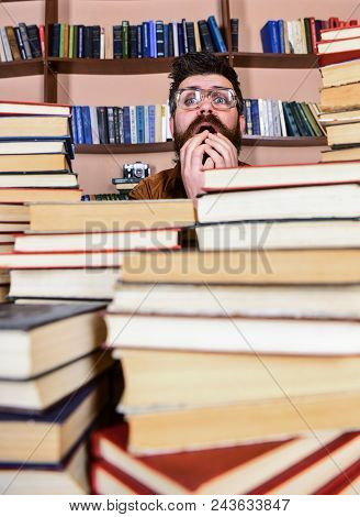 Man On Nervous Face Between Piles Of Books In Library, Bookshelves On Background. Teacher Or Student