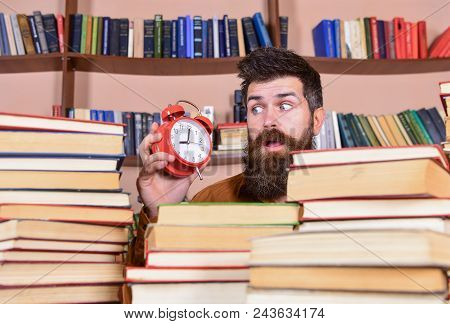 Teacher Or Student With Beard Studying In Library. Man, Scientist Peeking Out Of Piles Of Books With