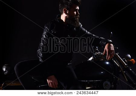 Brutality and masculine concept. Man with beard, biker in leather jacket lean on motor bike in darkness, black background. Macho, brutal biker in leather jacket stand near motorcycle at night time. poster