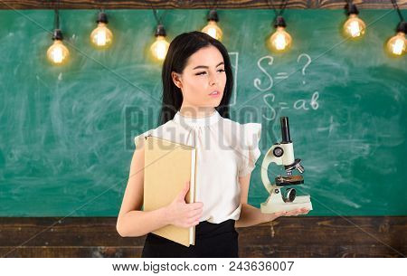 Lady In Formal Wear On Calm Face In Classroom. Biology Concept. Teacher Of Biology Holds Book And Mi