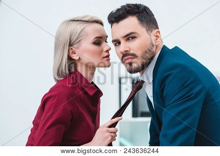 Young Businesswoman Holding Necktie Of Handsome Businessman Looking At Camera In Office