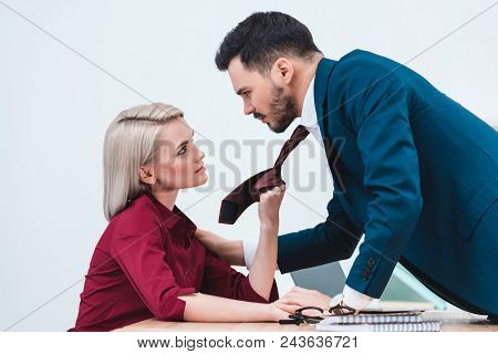 Side View Of Young Businesswoman Holding Necktie Of Handsome Businessman In Office