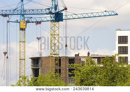 Urban View Of Silhouettes Of Two High Industrial Tower Cranes Working At Construction Of New Brick B