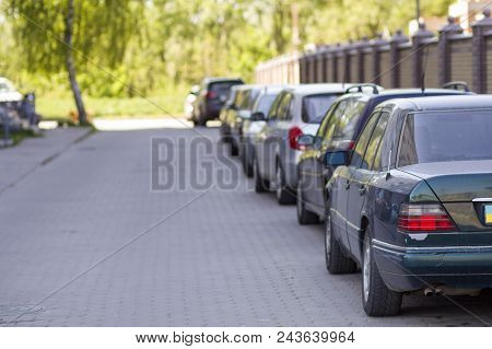 Long Row Of Cars Parked In Quiet Neighborhood On Clean Empty Paved Street Along New Stone Fence On B