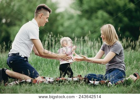 Happy Family Enjoy Weekend In Nature. Loving Parents Watch Their Daughter Doing First Steps. Baby Le