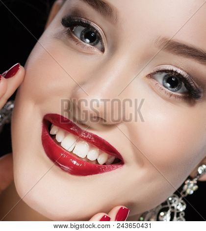 Beautiful brunette woman with bright make-up and jewelry earrings smiling close-up. Red lips and nails, evening make-up
