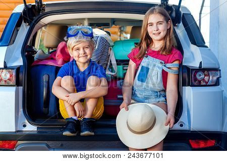 Little Sister And Brother Are Sitting In The Trunk Of A Car With Suitcases. Travel By Car Family Tri