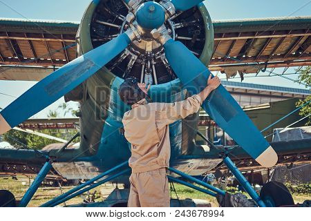 Pilot Or Mechanic In A Full Flight Gear Checks The Propeller Of His Retro Military Aircraft Before T