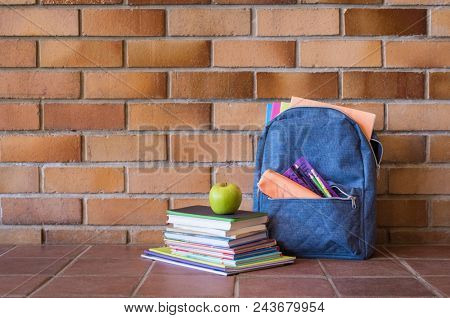Blue backpack with school supplies against brick wall. Full school bag with books and notebooks in a school hallway. Green apple on stack of books in a corridor. Back to school concept.