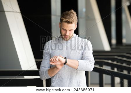 Man athlete on strict face checking fitness tracker, urban background. Athlete with bristle with fitness tracker or pedometer. Sportsman training with pedometer gadget. Sport gadget concept. poster