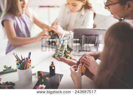 Outgoing Woman Holding Contemporary Toy In Hand. Happy Girls Creating Robot. Technology Concept