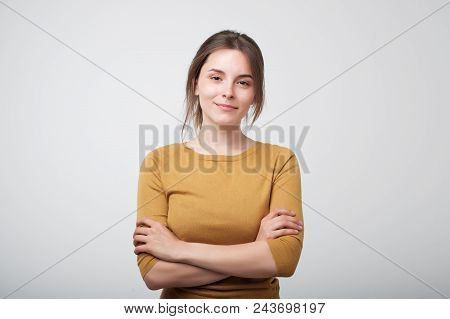Portrait Of Young Caucasian Woman In Yellow Shirt Casually Standing Near Gray Wall. Concept Of Being