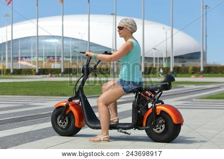 SOCHI, RUSSIA - JUL 09, 2017: woman on electric scooter on background of bowl of Olympic flame Firebird
