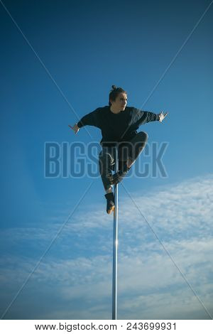 Athletic Guy Make Acrobatic Elements On Pylon. Sexy Macho Man Fly On Blue Sky Background. Young Man