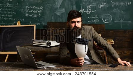 Bearded Man Hold Bulb In Classroom. Scientist Hipster With Lightbulb On Chalkboard. Businessman In S