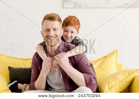 Happy Redhead Father And Son Hugging And Smiling At Camera At Home