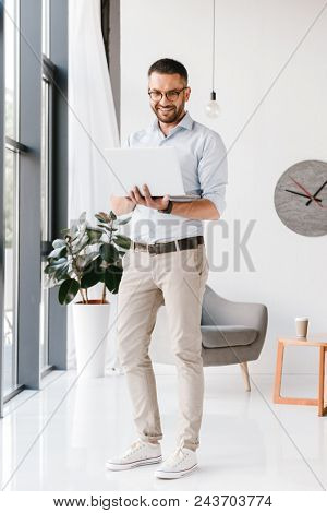 Full length photo of confident business man wearing white shirt looking at silver laptop while standing and working in business room