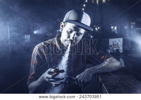 Hipster In A Cap Sits On A Bench And Playing With A Fidget Spinner. Toned Image. Concept Of Youth Li