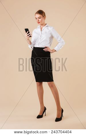 Full length portrait of a confident businesswoman texting on mobile phone isolated over beige background