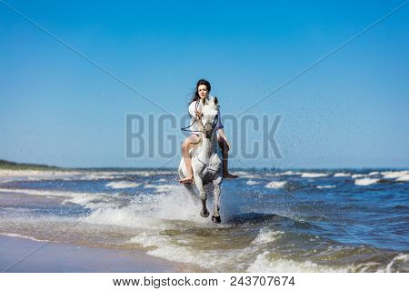 Girl riding on a white horse in the sea with water splashing around. Galopade. Summer.