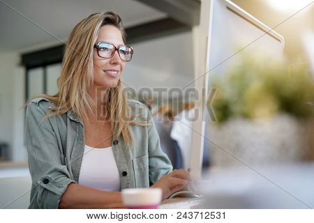 Beautiful woman working on desktop computer, co-working area