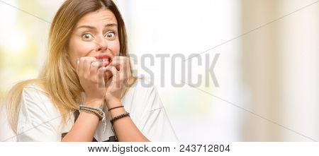 Shop owner woman wearing apron terrified and nervous expressing anxiety and panic gesture, overwhelmed
