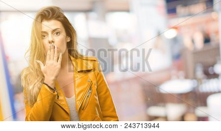 Beautiful young woman covers mouth in shock, looks shy, expressing silence and mistake concepts, scared at restaurant
