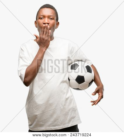 African black man holding soccer ball covers mouth in shock, looks shy, expressing silence and mistake concepts, scared