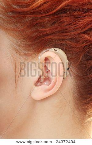 Redhead woman wearing hearing aid