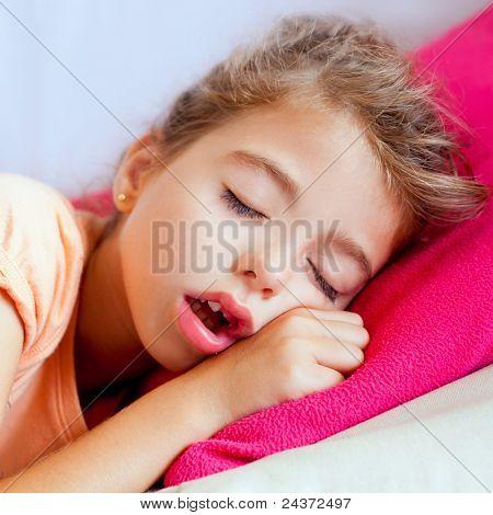 Deep sleeping children girl closeup portrait on pink pillow