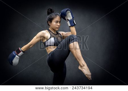 Young Asian Woman Boxer With Blue Boxing Gloves Kicking In The Exercise Gym, Martial Arts On Black B