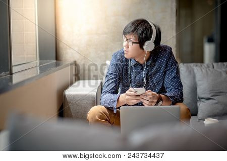 Young Asian Man With Headphones Using Smartphone For Listening To Music, Taking A Break And Relaxing