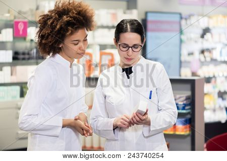 Two experienced female pharmacists wearing lab coats while analyzing together the package of a new pharmaceutical drug in the interior of a modern pharmacy