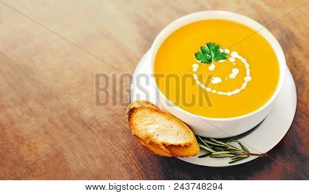 Pumpkin And Carrot Soup In A White Bowl  On Rustic Wooden Table. Autumn Cream Soup Top View