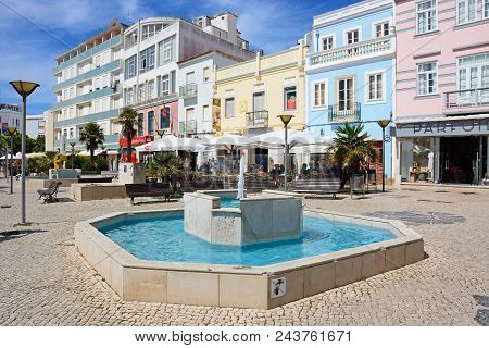 Lagos, Portugal - June 9, 2017 - Fountain And Cafes Along The R. Da Porta De Portugal In The Old Tow