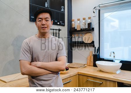 Young Handsome Asian Man Prepare Salad Food And Cooking In The Kitchen. Young Asian Male Spend Free