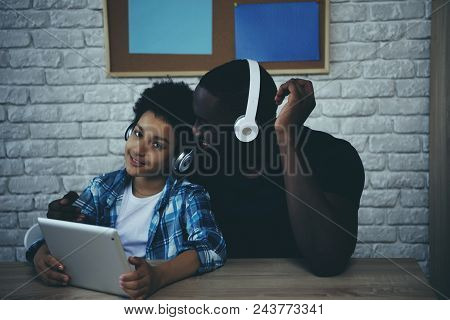 Black Teen Boy In Headphones Listening To Music With Father. Selection Of Songs In Player. Fatherhoo
