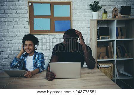 Teen Boy In Headphones Listens Loudly To Music And Prevents Busy Father From Working. Fatherhood.