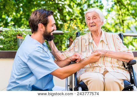 Geriatric nurse holding hand of happy old woman in rest home