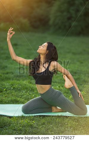 Woman Practicing Yoga Performing Yoga-asanas. Young Attractive Slim Girl In Bodysuit Relaxing And Do