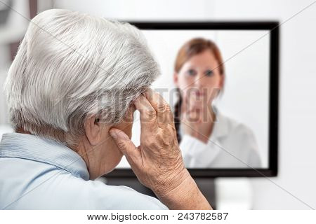 Elderly Woman With Headache, Doctor On The Monitor Listening, Concept Telemedicine And Consultation