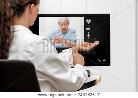 Doctor And Senior Woman Taking The Pulse Together, Telemedicine And Videotelephony For Medical Healt